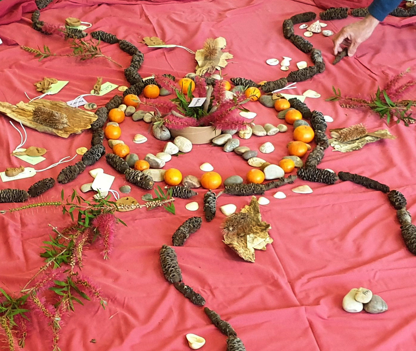 Nature collage with sticks and rocks on red fabric floor